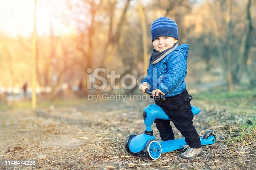 665192886 istock photo Cute adorable caucasian toddler boy in blue jacket having fun riding three-wheeled balance run bike scooter in city park or forest. Children outdoor sport activities 1146474228