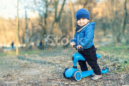 665192886 istock photo Cute adorable caucasian toddler boy in blue jacket having fun riding three-wheeled balance run bike scooter in city park or forest. Children outdoor sport activities 1163408400
