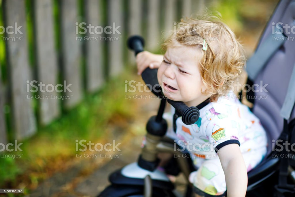 Cute adorable crying sad toddler girl sitting on pushing bicyle or tricycle. Little baby child going for a walk with parents on sunny day. stock photo