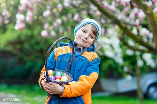istock Cute adorable little kid boy making an egg hunt on Easter. 917722680