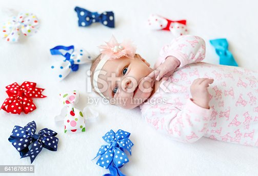 istock cute adorable newborn baby child with colorful bows 641676818