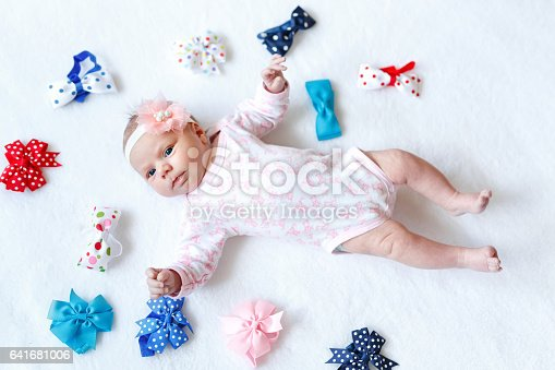 istock cute adorable newborn baby child with colorful bows 641681006