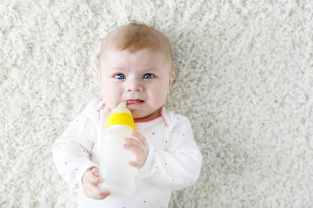Cute adorable newborn baby girl holding nursing bottle and drinking formula milk stock photo