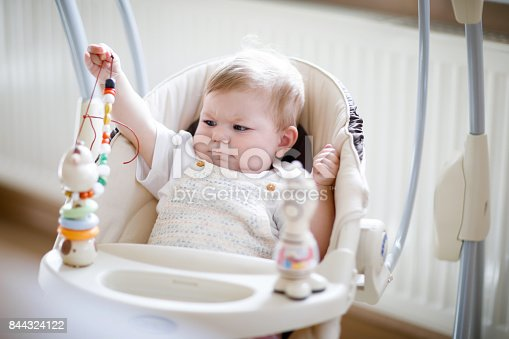 istock Cute adorable newborn baby girl sitting in swing indoors 844324122