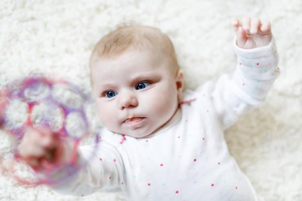 Süße entzückende Neugeborene Baby spielen mit bunten Ball Spielzeug auf weißem Hintergrund. Neugeborenes Kind, kleines Mädchen, das in die Kamera schaut. Familie, neues Leben, Kindheit, Anfangskonzept. Baby lernen greifen Rassel. – Foto