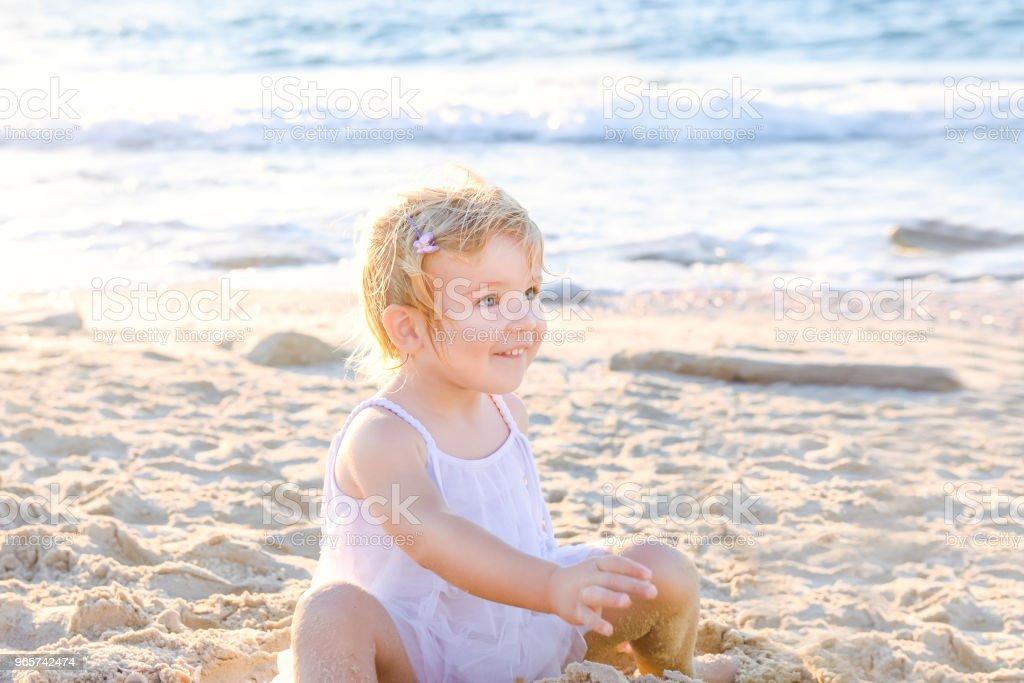 Een schattig schattige lachende peuter meisje in witte kleding spelen met zand en schelpen op het strand op een warme zonnige zomerdag. Vakantie aan zee. Familie vakantie. Achtergrondverlichting. Selectieve aandacht, kopie ruimte. - Royalty-free Activiteit Stockfoto