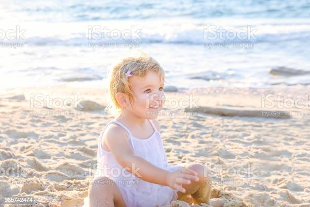 A Cute Adorable Smiling Toddler Girl In White Clothes Playing With Sand And Shells On The Beach On A Warm Sunny Summer Day Holidays At Sea Family Vacation Backlight Selective Focus Copy Space - Fotografias de stock e mais imagens de Alegria