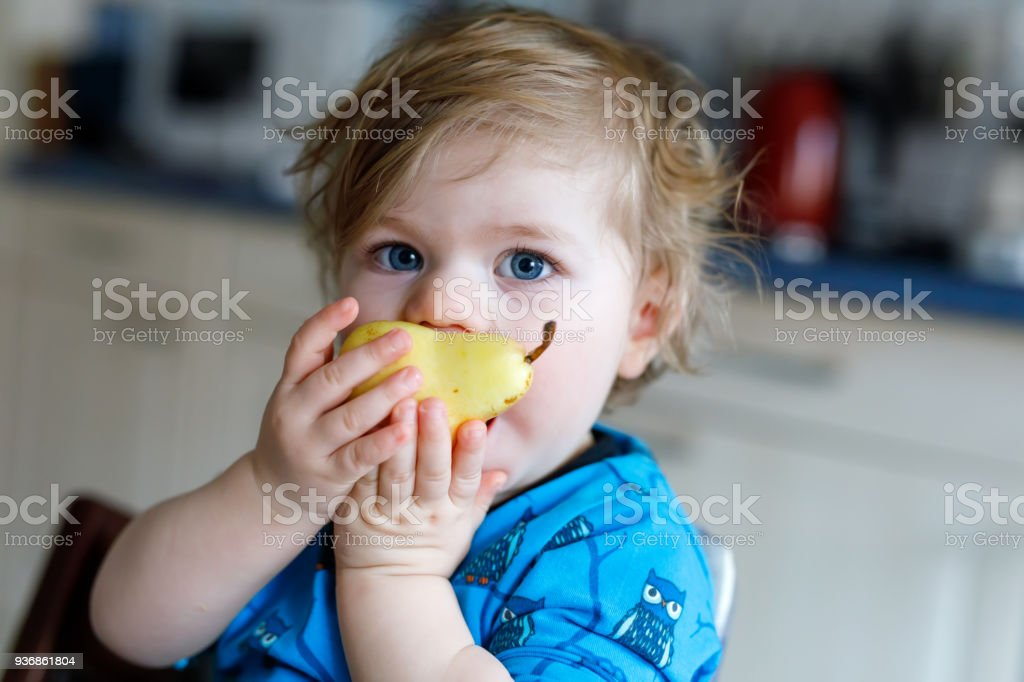 Cute adorable toddler girl eating fresh pear . Hungry happy baby child of one year holding fruit. stock photo