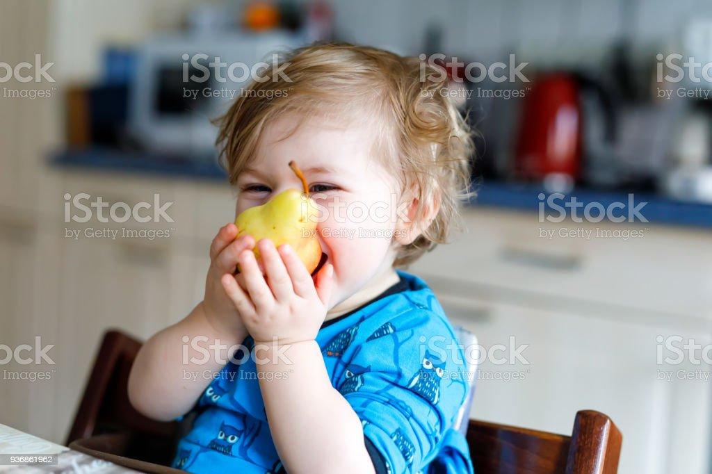 Cute adorable Kleinkind Mädchen essen frische Birne. Hungrige glückliches Baby Kind von einem Jahr hält Obst. – Foto