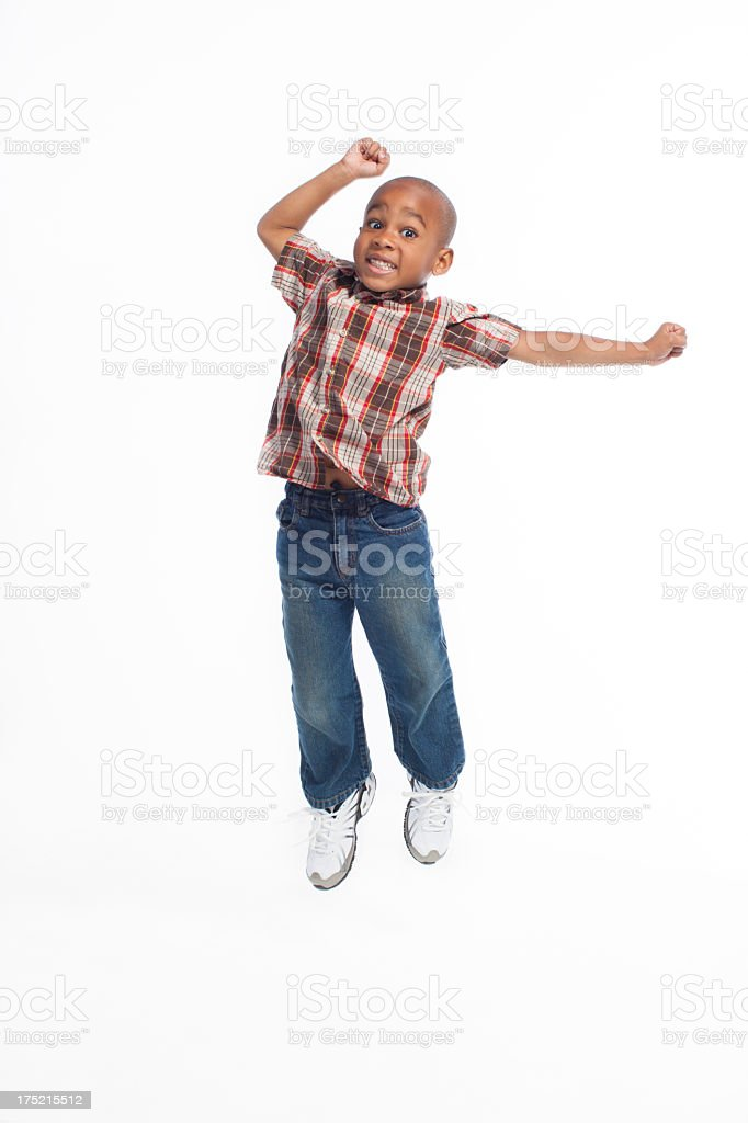 Cute African American boy jumping in the air. stock photo