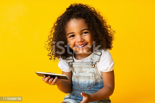 Cute african american girl holding cellphone and smiling over yellow background