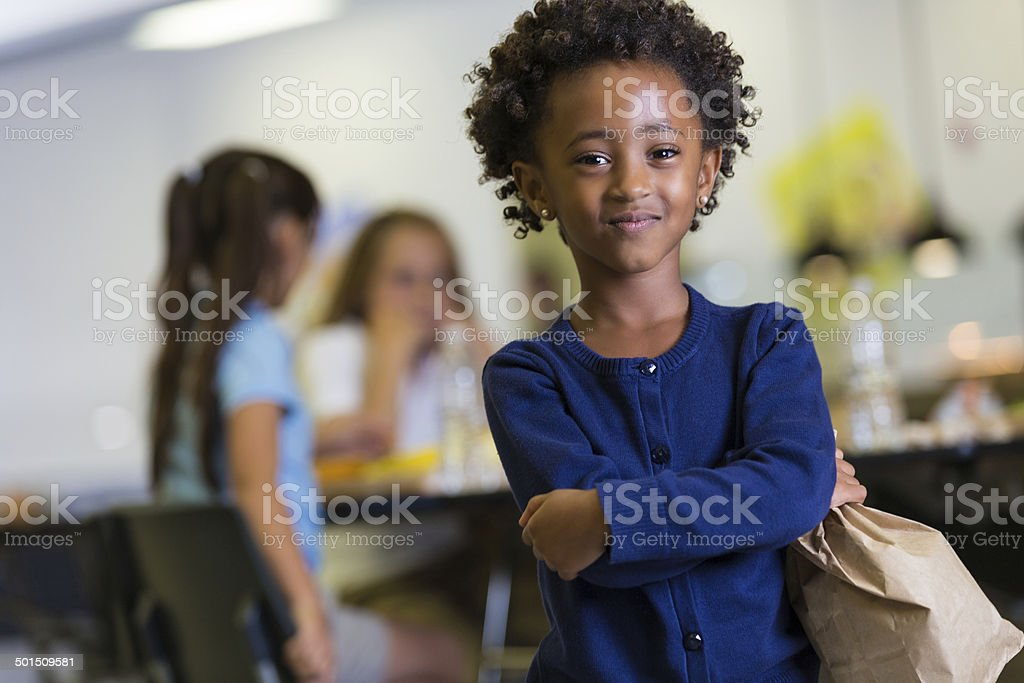 Cute African American girl holding paper lunch sack in cafeteria stock photo