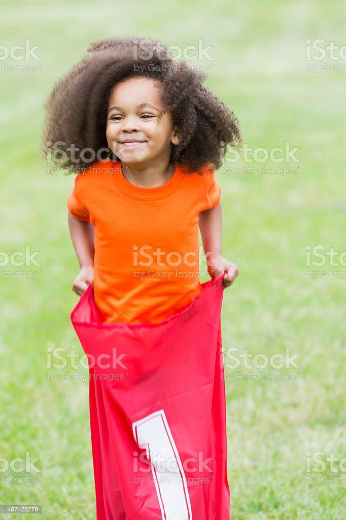 Cute African American girl in potato sack race stock photo