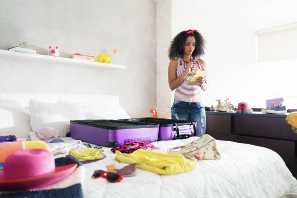 Cute African American Girl Packing Bag For Holiday And Travel stock photo