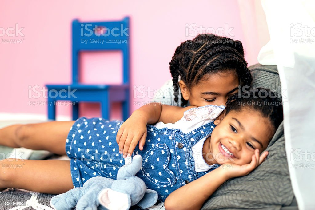 Cute African American girls relaxing together on the floor stock photo
