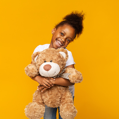 istock Cute african american little girl embracing her teddy bear and smiling 1174447822