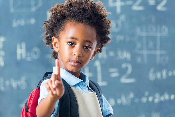 Cute African American private school child holding up one finger stock photo