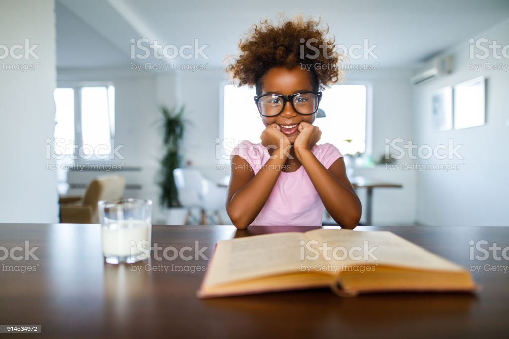 Cute African American schoolgirl reading a book at home stock photo