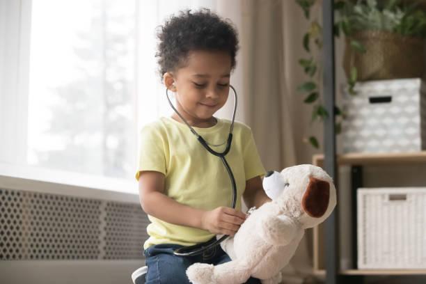menino africano bonito que joga com brinquedo como o doutor que prende o estetoscópio - brincadeira - fotografias e filmes do acervo