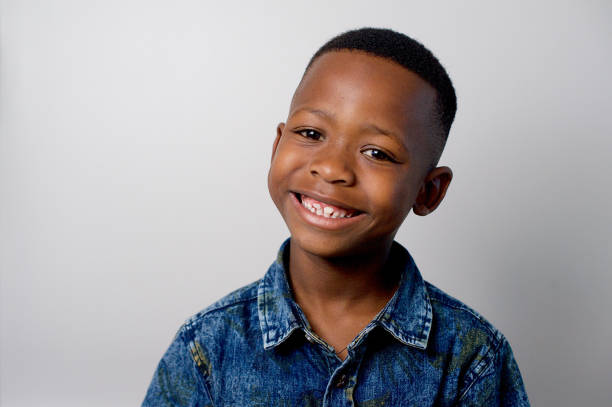 Cute African boy smiling portrait Cute African boy smiling head and shoulders Formal portrait with studio lighting Strand Cape Town South Africa 6 7 years stock pictures, royalty-free photos & images