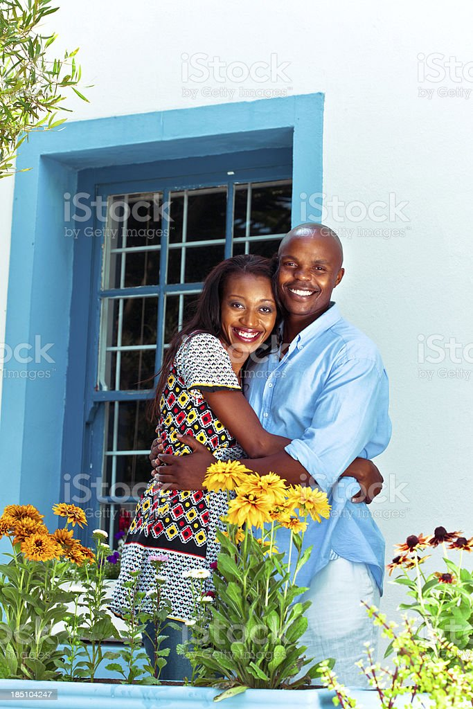 Cute african couple Happy african couple embracing in front of their house. Adult Stock Photo