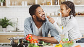 African girl feeding dad in kitchen, giving him cherry tomato while cooking salad, copy space
