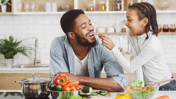 Cute african girl giving her dad cherry tomato while cooking African girl feeding dad in kitchen, giving him cherry tomato while cooking salad, copy space eating stock pictures, royalty-free photos & images