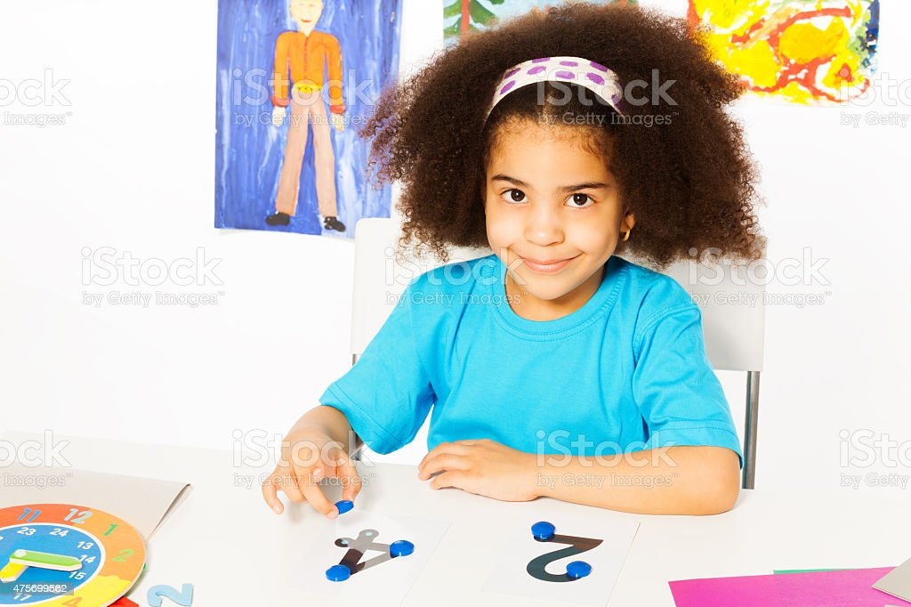 Cute African girl learn numbers with coins stock photo