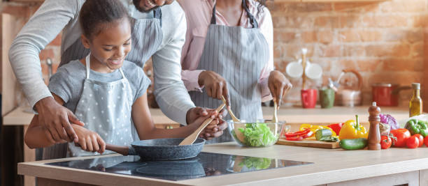 cute african girl learning how to cook healthy meal - cooker happy imagens e fotografias de stock