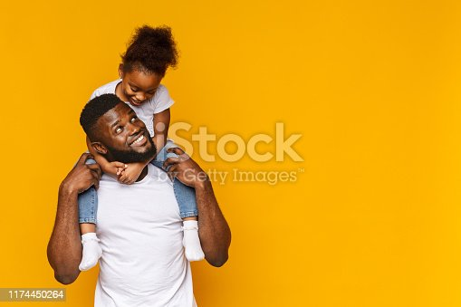 Happy moments. Cute african girl sitting on daddy's shoulders, orange background, empty space