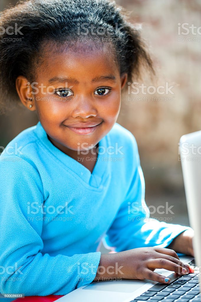 Cute african girl typing on laptop. stock photo