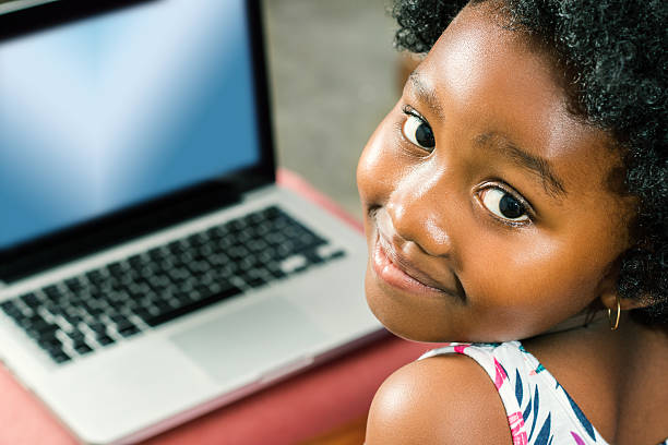 Cute african girl with laptop in background. stock photo