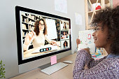 istock Cute african kid child girl showing homework talking to remote teacher distance learning during virtual online class on video conference call with tutor and school children group at home on computer. 1284585957