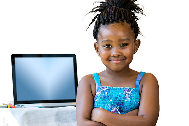 Cute african kid standing with laptop in background. stock photo