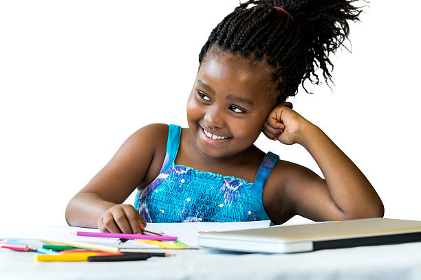 Cute african student at desk with color pencils. stock photo