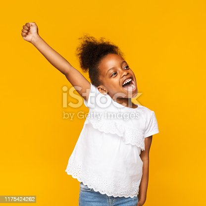 istock Cute african toddler girl shouting hooray on orange background 1175424262