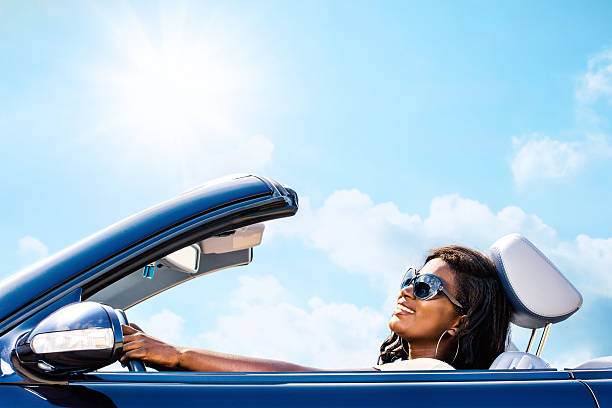 Cute african woman driving convertible. stock photo