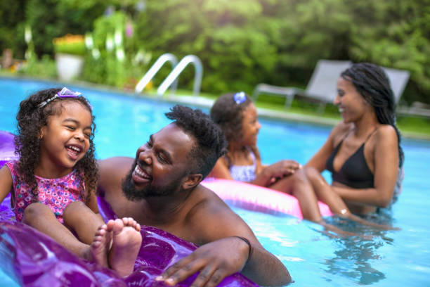 Cute African-American family with two daughters swimming at backyard pool stock photo