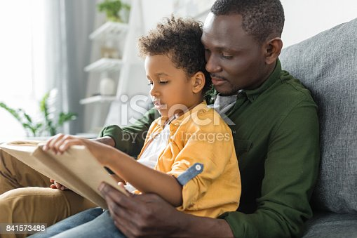 istock cute african-american father and son reading book together 841573488