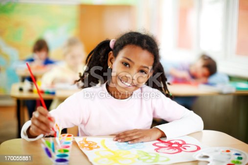 172364312 istock photo Cute African-American girl is painting with watercolors. 170055881