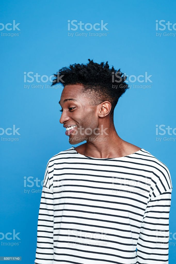 Cute afro american guy, studio portrait against blue background Studio portrait of cute, happy afro american young man wearing striped top. Studio portrait, blue background. Adult Stock Photo