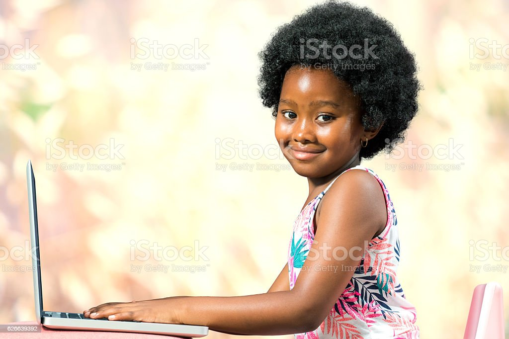 Cute afro american kid typing on laptop. stock photo
