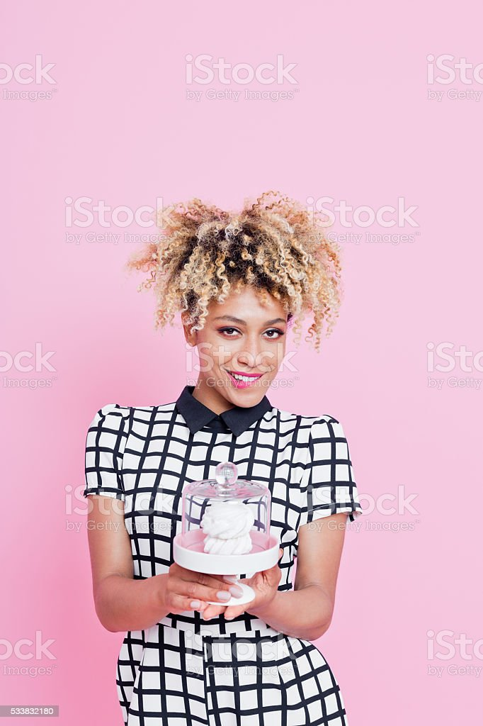 Cute afro american small business owner holding cookies Summer portrait of happy, afro american young woman wearing grid check playsuit, standing against pink background, holding cookies and smiling. Studio shot, pink background.  25-29 Years Stock Photo