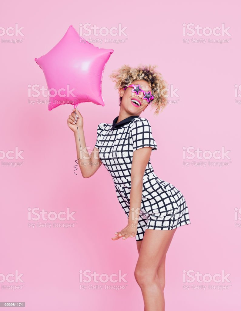 Cute afro american woman holding pink balloon Studio portrait of cute afro american young woman holding pink balloon. Pink background. 20-24 Years Stock Photo
