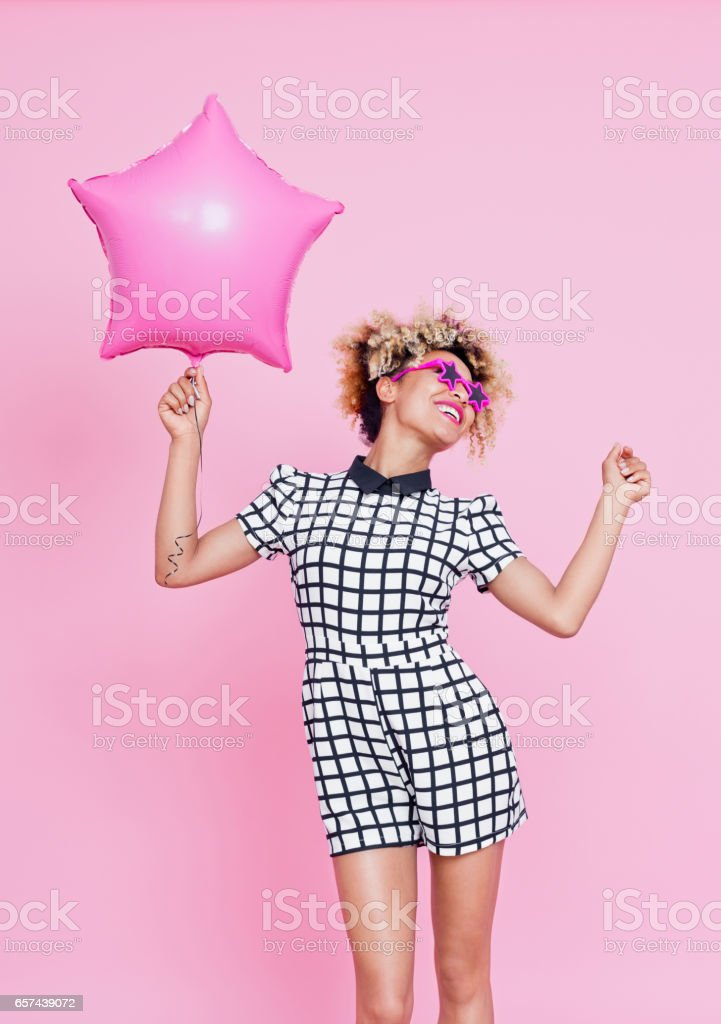 Cute afro american woman holding pink balloon Studio portrait of happy afro american young woman holding pink balloon. Pink background. 20-24 Years Stock Photo