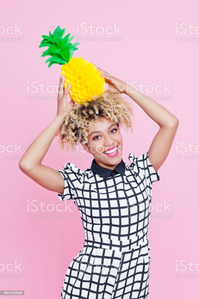 Cute afro american young woman holding paper pineapple Studio portrait of cute afro american young woman holding a paper pineapple . Pink background. 20-24 Years Stock Photo