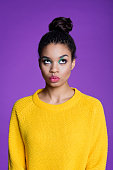 Fashion portrait of beautiful afro american young woman wearing yellow sweater. Studio shot, violet background.