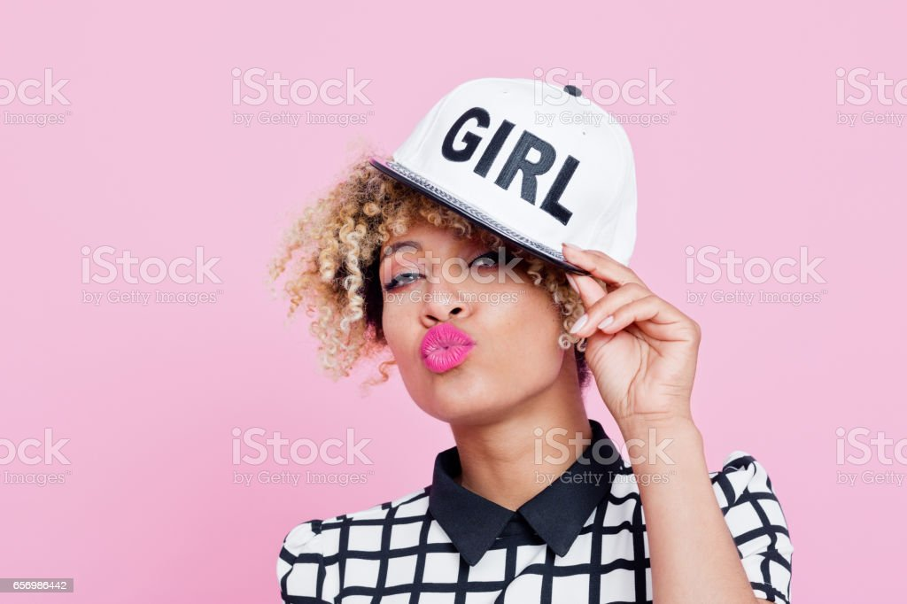 Cute afro american young woman Studio portrait of cute afro american young woman wearing baseball cap, blowing kiss. Pink background. 20-24 Years Stock Photo