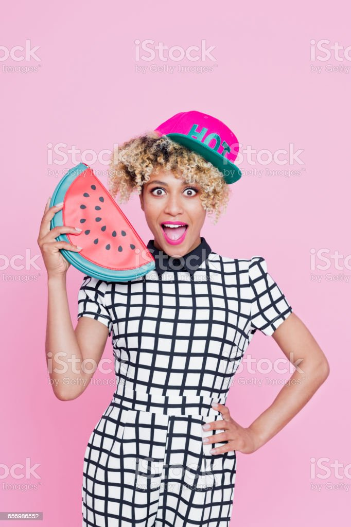 Cute afro american young woman Studio portrait of surprised afro american young woman wearing baseball cap and holding watermelon and staring at camera. Pink background. 20-24 Years Stock Photo