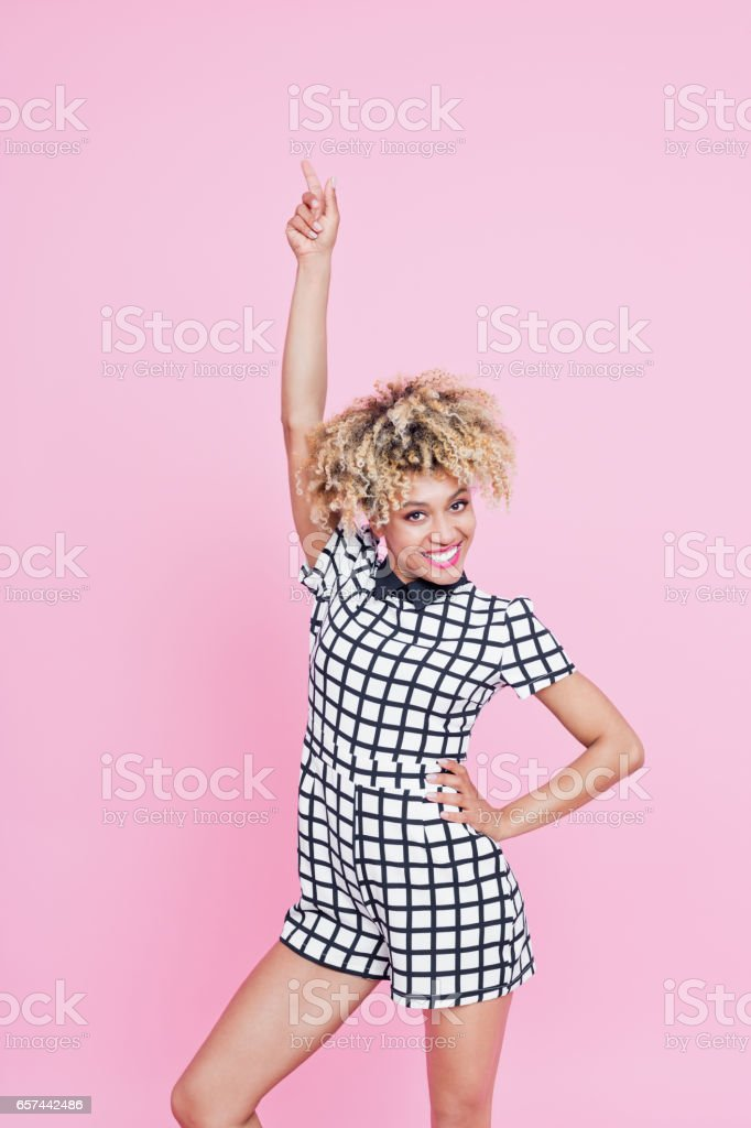 Cute afro american young woman pointing at copy space Studio portrait of happy afro american young woman pointing at copy space. Pink background. 20-24 Years Stock Photo